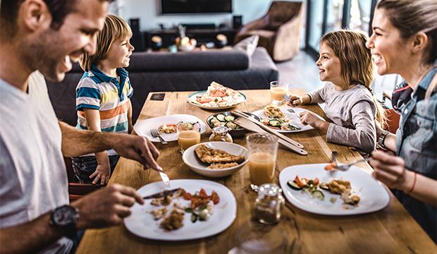 Veľká šťastná rodina obeduje za jedálenskym stolom.