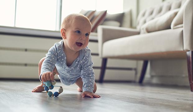 Chlapček lezie po podlahe.