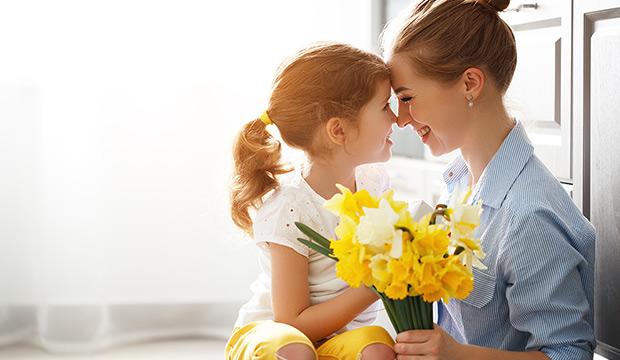 dcera dává matce kytici narcisů