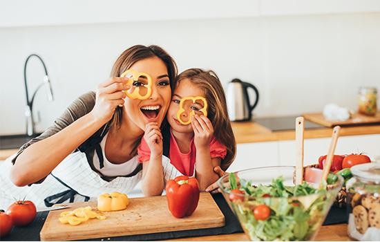 máma a dcera se baví při vaření v kuchyni
