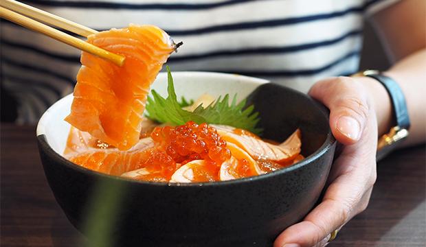 zdravá miska plná plátků nakrájeného lososa