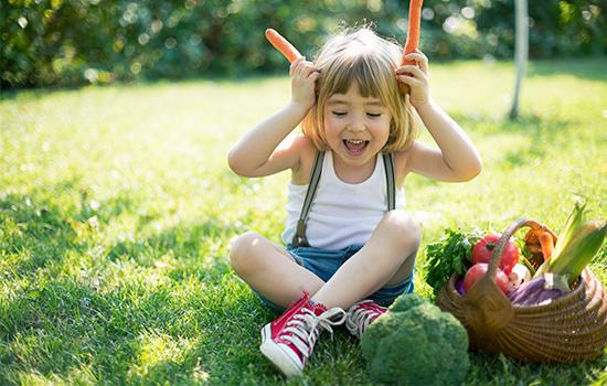 dítě s košíkem organické zeleniny