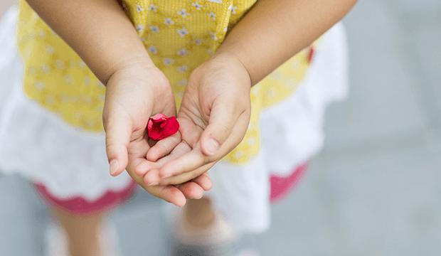 dieťa držiace lupene kvetov