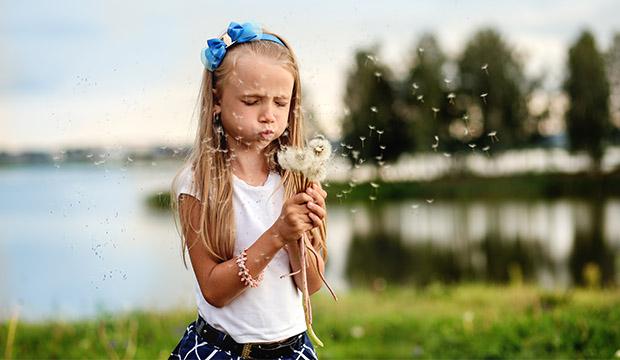 dievča fúkajúce do púpavy počas letných dní