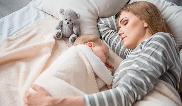 máma odpočívající s dítětem na posteli