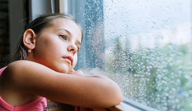 Smutné dievča pozerajúce sa von oknom.