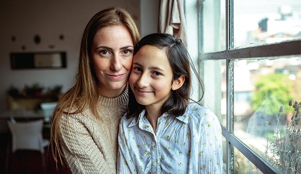 Fotka matky a její dcery, které sedí doma.